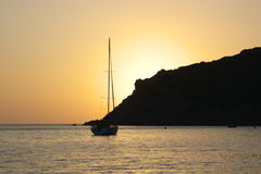 Sunset with cliff and yacht Stock Image