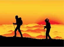 Sunset climbers. A man and a woman climbing a mountain at sunset Stock Photography