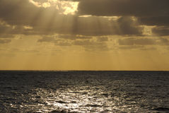 Sunset Cloudburst at Sea. The golden rays of a sunset at sea bursts through the clouds Stock Photos