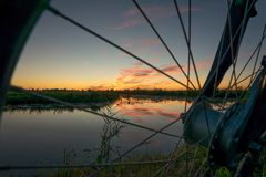 A beautiful sunset with reflections in the calm water of a lake, as seen through the wheel of a bicycle stock images