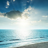 Sunset in clouds and blue sea Stock Image