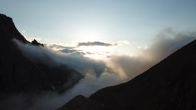 At sunset, clouds fly into the gorge. The rays of the outgoing sun are seen beyond the horizon. And the rocks spread to the sides royalty free stock images
