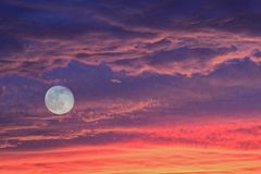 Sunset clouds & full moon Royalty Free Stock Photo