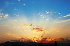 Sunset with clouds, light rays, blue sky, natural background. at Stock Photography