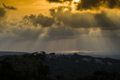 Sunset through the clouds with light rays royalty free stock photography