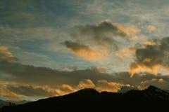 Sunset with clouds and mountai Stock Photos