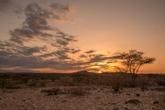 Sunset through the clouds over an arid desert landscape of sand stock photos