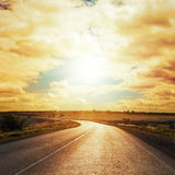 Sunset in clouds over asphalt road Royalty Free Stock Image