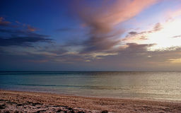 Sunset clouds over beach. Colorful sunset clouds over sea with beach in the foreground Stock Images