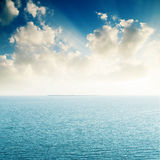 Sunset in clouds over blue sea. Good sunset in clouds over blue sea Stock Photos
