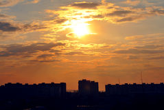 A sunset through the clouds over buildings. Summer sunny day with a big yellow sun that sat through clouds and wants to fade royalty free stock photos