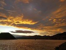 Sunset clouds over the lake. Beautiful orange clouds over the lake, at sunset Stock Photo