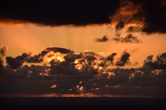 Sunset through the clouds over the ocean stock photography