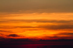 Sunset in clouds over red sunset sky background. Stock Images