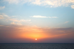 Sunset with clouds over the smooth sea Stock Images