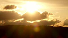 Sunset in clouds and over tops fir trees. Time lapse. Sunset in clouds and over tops fir trees, hilly area with forests, bright sun hides behind horizon and stock footage