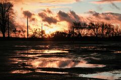 Sunset clouds after the rain over field with puddles