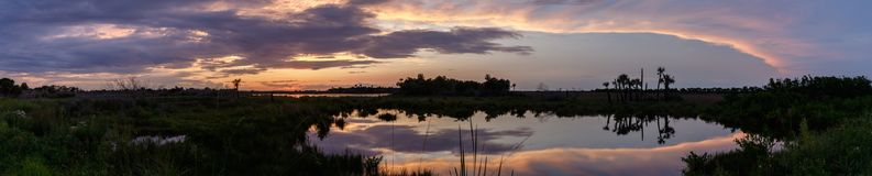 Sunset at Merritt Island National Wildlife Refuge, Florida. Sunset with clouds reflecting in a pond at Merritt Island National Wildlife Refuge, Florida, USA royalty free stock image