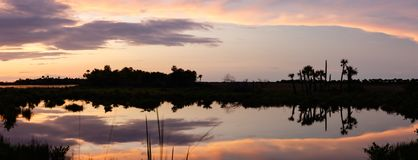 Sunset at Merritt Island National Wildlife Refuge, Florida. Sunset with clouds reflecting in a pond at Merritt Island National Wildlife Refuge, Florida, USA stock photography