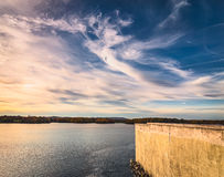 At sunset. Clouds and river near dock wall at sunset Stock Photography