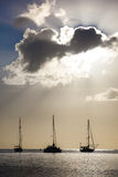 Sunset through clouds, with sailboats on the horizon in the Cari Royalty Free Stock Photography