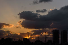 Sunset in clouds. Sun sets behind clouds still revealing skyline of town - Petach Tikva, Israel stock image