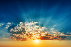 Sunset in clouds and sunrays over it Stock Photos