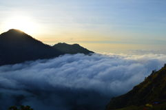 Sunset and clouds. The sunsets on Mt Rinjani Indonesia the cloud rolls in over the volcano enveloping all but the top Royalty Free Stock Images