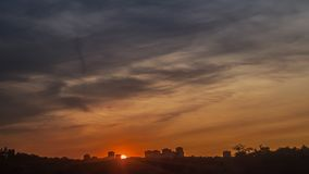 Sunset in clouds. Timelapse of sunset in clouds with high rise building silhouettes on horizon stock video footage
