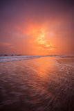 Sunset clouds and waves on empty beach Royalty Free Stock Images
