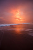 Sunset clouds and waves on empty beach Stock Images