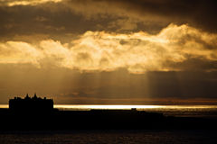 Sunset and cloudscape over sea. Scenic view of hotel building silhouetted and sunset under cloudscape, Newquay, Cornwall, England Royalty Free Stock Photos
