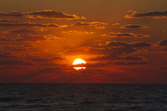 Sunset and cloudscape over sea. Red sunset and cloudscape over calm sea Royalty Free Stock Photos