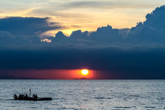 Sunset with cloudy sky and boat on the sea Stock Photos