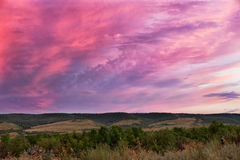 Sunset in cloudy sky over hilly field Royalty Free Stock Images