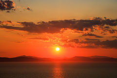 Sunset in cloudy sky over mountains and sea Stock Photography