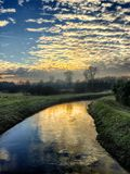 Sunset cloudy sky reflected in the river. Sunset sky with altocumulus clouds reflected in the water of the river Royalty Free Stock Images