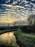 Sunset cloudy sky reflected in the river. Sunset sky with altocumulus clouds reflected in the water of the river Royalty Free Stock Photography