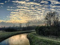Sunset cloudy sky reflected in the river. Sunset sky with altocumulus clouds reflected in the water of the river Royalty Free Stock Photo