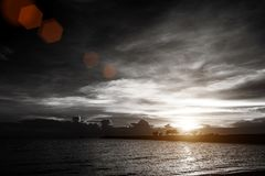Sunset on cloudy sky at sea beach with silhouette rock bridge Royalty Free Stock Images