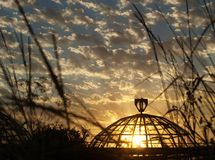 Sunset cloudy sky and sun behind the glass of an old greenhouse stock photos