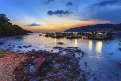 Sunset at coast with fishing boats Stock Photo