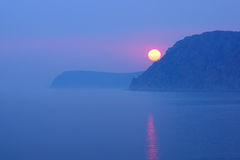 Sunset on the coast in the fog with a large sun. In the frame Stock Image