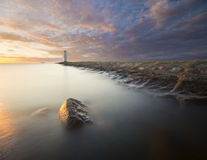 Sunset on the coast, lighthouse windmill in Swinoujscie, Poland. Stock Images