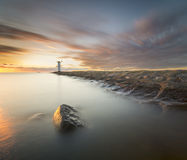 Sunset on the coast, lighthouse windmill in Swinoujscie, Poland. Royalty Free Stock Images