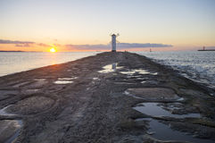 Sunset on the coast, lighthouse windmill in Swinoujscie, Poland. Stock Photography