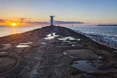 Sunset on the coast, lighthouse windmill in Swinoujscie, Poland. Royalty Free Stock Photography