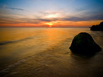 Sunset at coast of the sea. Sunset at the sea with silhouette of stones with small waves Royalty Free Stock Images