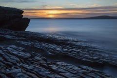 Sunset of coast with wet rocks. Coastal sunset with long exposure on waves, wet rocks, Isle of Skye, Scotland Stock Photos