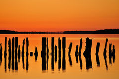 Sunset at Rugen island. Pylons and coastline silhouetted in glowing sunset. Island of Rugen, Germany Royalty Free Stock Photos